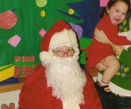 Sad toddler with Santa, scared of Santa